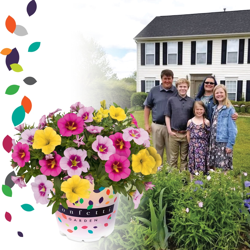 A group of people standing around a cake with flowers  Description automatically generated with low confidence